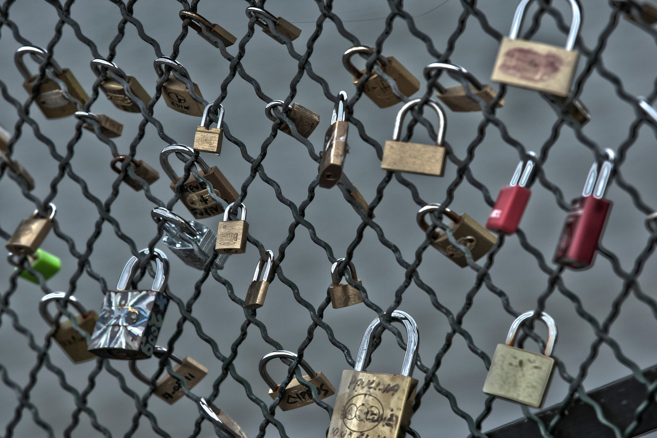 Padlocks - signs of love and affection on a grill on a bridge in Paris, France.